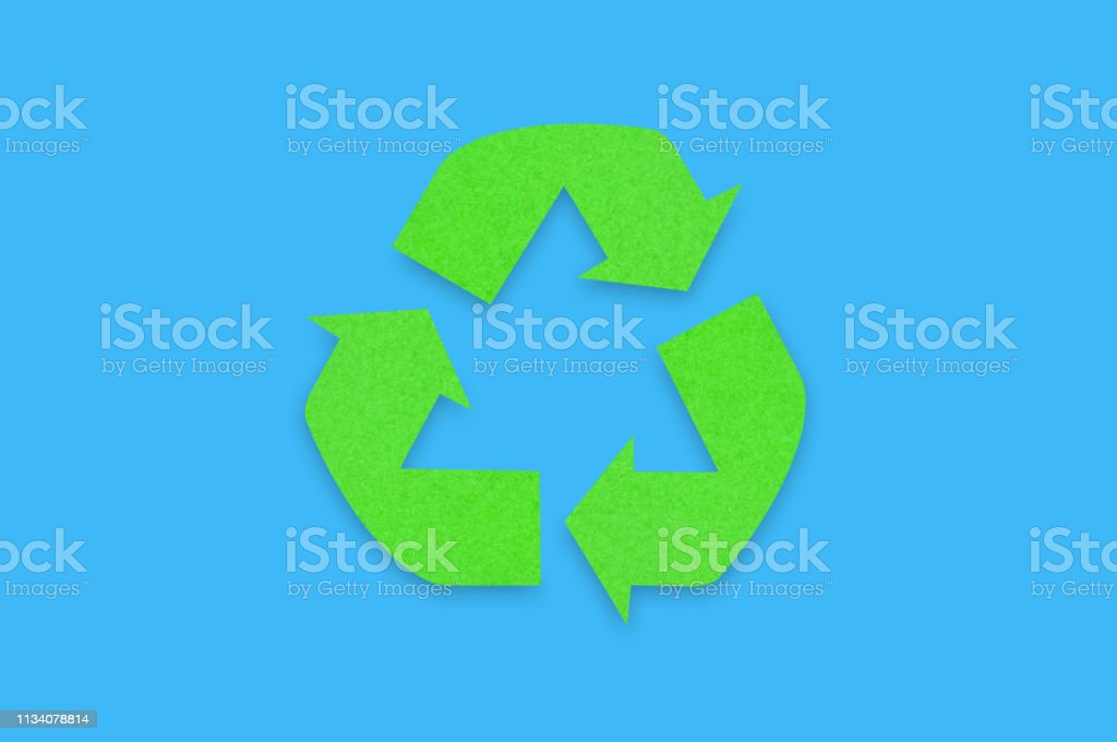 Symbol of eco recycling cut out of green paper on blue background....