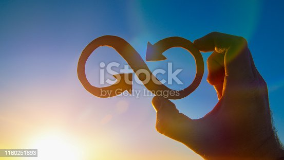 istock A symbol of infinity in the hand of a man against the sky and the glare of the sun, business concept idea. 1160251693