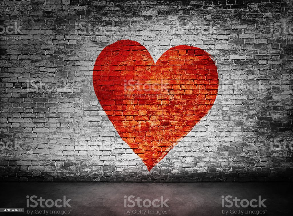 Symbol of love painted on murky brick wall stock photo