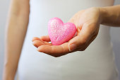 Pink heart in hand. Symbol of love, giving and compassion.