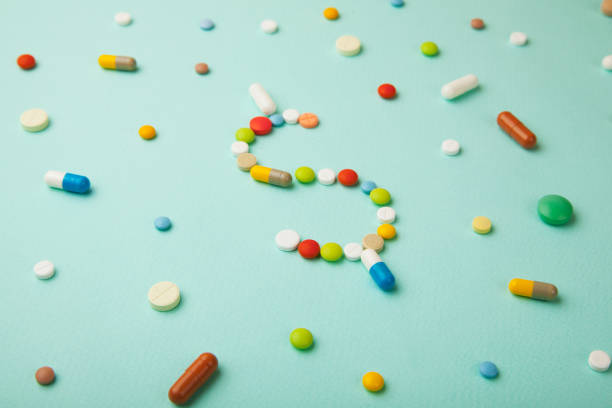 Symbol of money dollar from colored pills and capsules on  green background. Expensive medicine and medical insurance stock photo