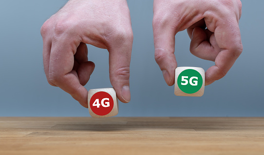istock Symbol of selecting the new mobile standard 5G over 4G. Hand picks the cube with the label