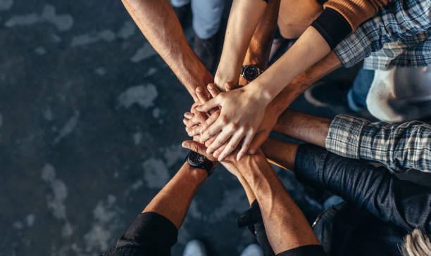 Symbol of teamwork, cooperation and unity Top view of creative professionals putting their hands together as a symbol of teamwork, cooperation and unity. Stack of hands of men and woman. collaboration stock pictures, royalty-free photos & images