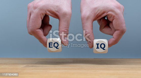 Symbol of the balance between emotional intelligence and the intelligence quotient.  Hands are holding two dice with the letters