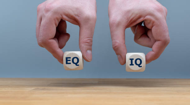 "symbol of the balance between emotional intelligence and the intelligence quotient.  hands are holding two dice with the letters ""eq"" and ""iq"" in front of a grey background. - intelligence zdjęcia i obrazy z banku zdjęć"