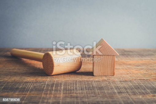 istock Symbol of worldwide real estate crisis. wood hammer and house with filter effect retro vintage style 838795636