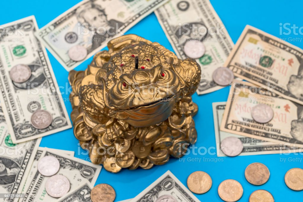Symbol toad and dollar coin and banknote isolated on blue stock photo