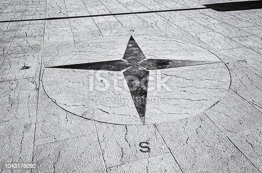 Symbolic compass on the ground, Trogic, Croatia. Travel destination. Black and white photo.