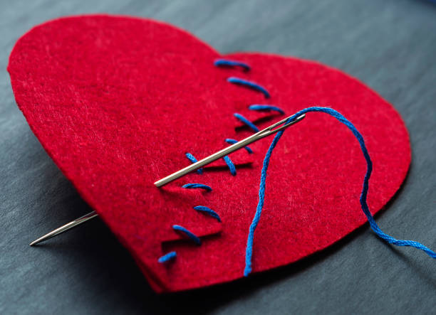 Symbolic image of broken heart. Textile red heart sewn with a needle and thread. Selective focus. Symbolic image of broken heart. Textile red heart sewn with a needle and thread. Selective focus. red broken heart sewn threads stock pictures, royalty-free photos & images