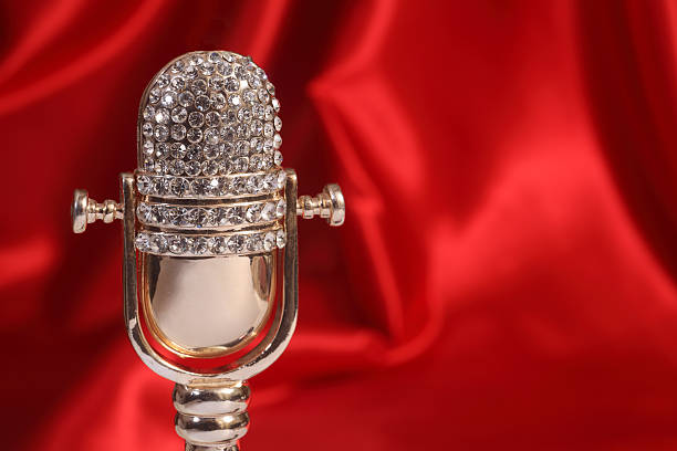 Symbolic microphone on red fabric stock photo