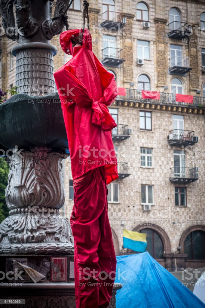 Symbolic red dummy doll hanging from a street lamp on a street near the Freedom square in Kiev Ukraine. royalty-free stock photo