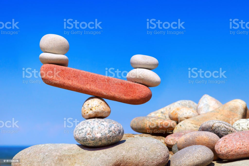 Symbolic scales from stones. The disturbed equilibrium. Imbalance concept. stock photo