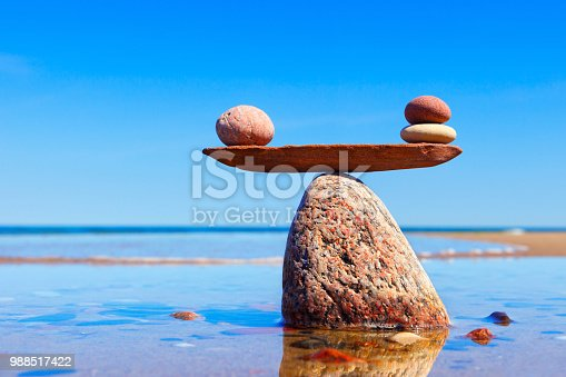 istock Symbolic scales made of stones on the sea background. Concept of harmony and balance. 988517422