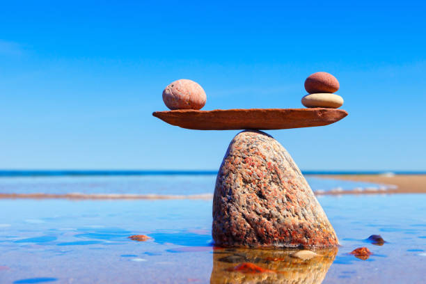 Symbolic scales made of stones on the sea background. Concept of harmony and balance. stock photo