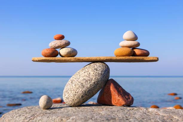 symbolische schuppen der steine gegen das meer. vor- und nachteile - gleichgewicht stock-fotos und bilder