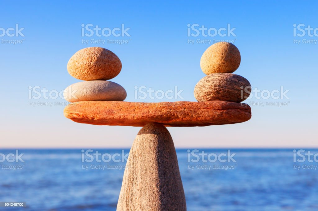 Symbolic scales of the stones, illuminated by the evening sun, against the sea, close-up. Pros and cons concept stock photo