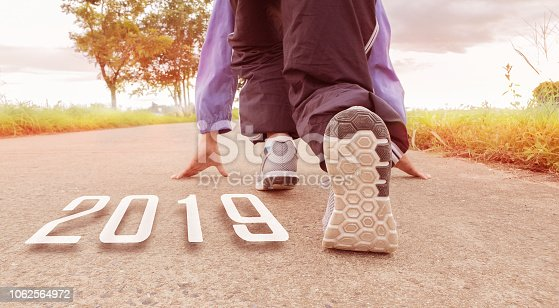 istock 2019 symbolises the start into the new year.Start of people running on street,with sunset light.Goal of Success 1062564972
