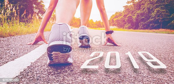 istock 2019 symbolises the start into the new year.Start of people  running on street,with sunset light.Goal of Success 975765500