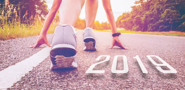 2019 symboliserar början in det nya året. början av folk som kör på gata, med solnedgången ljus. målet med framgång - calendar workout bildbanksfoton och bilder