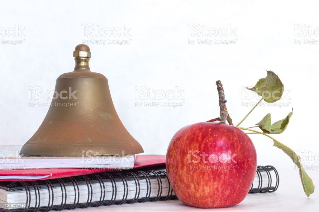 Symbols for education, red delicious homegrown apple, brass school bell stacked on black spiral bound sketch notebook, red folder and composition book isolated on white background stock photo