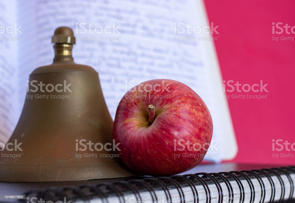 Symbols for education, red delicious homegrown apple, brass school bell stacked on black spiral bound sketch notebook, red folder and composition book with writing in background stock photo