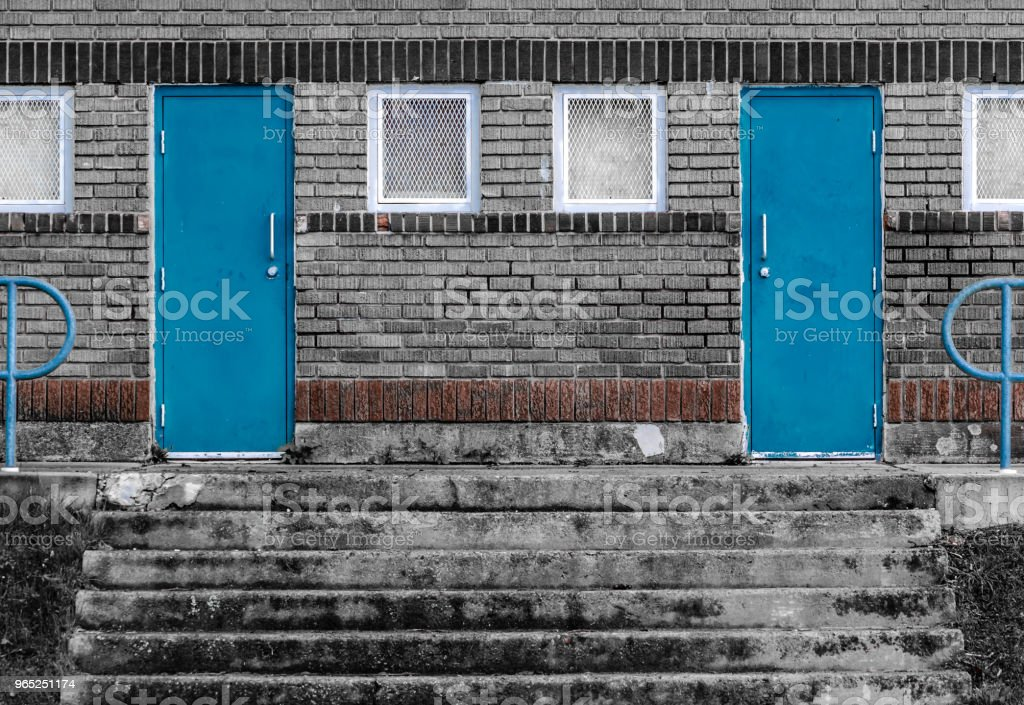 Symetrical Blue doors on black and white brick building royalty-free stock photo