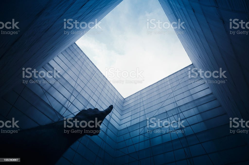 Symmetric contemporary architecture with finger pointing stock photo