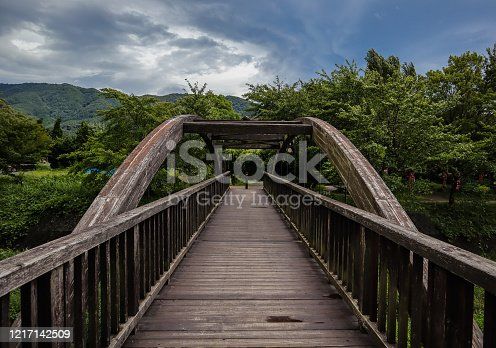 Remote wooden bridge on symmetry with clouds and trees in the backgound