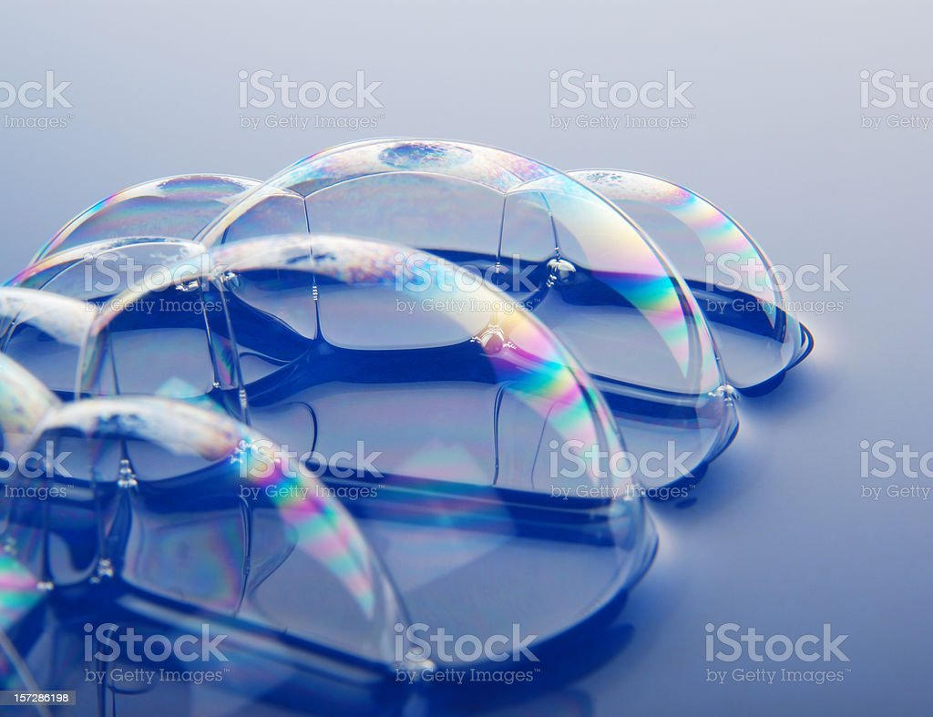 Symmetrical dome shaped bubbles on blue background royalty-free stock photo