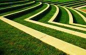 this photo is of Green Grass Lawn with Rows of Steps at a Park. the lawn is lush green grass in an abstract row setting. the lawn has been mowed. and the shaped on the rows are in a unique layout. the picture was taken during the spring or summer. and the lighting is natural sunlight.