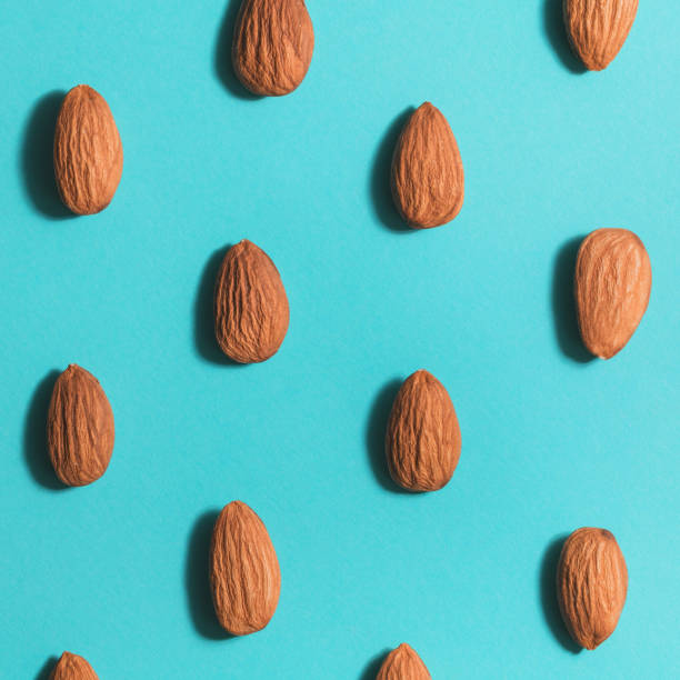 Symmetrical pattern of almonds on blue. Flat lay. stock photo