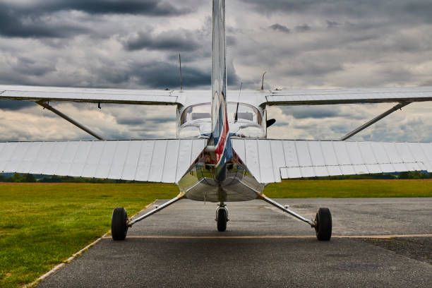Symmetrical rear view of Cessna 172 Skyhawk 2 airplane on a runway with dramatic sky background. stock photo