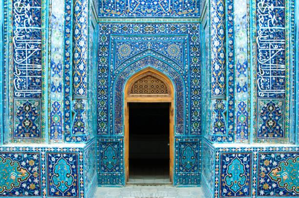 symmetrisch, rijkelijk versierd met blauwe keramische islamitische tegels, entree en open deur in shah-i-zinda - oezbekistan stockfoto's en -beelden