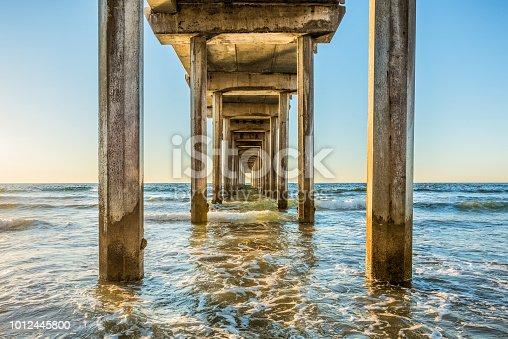 Symmetrical shot under Scripps Pier with poles, pillars, sunny sunlight, sun, blue sky, waves during golden sunset in La Jolla, San Diego, California