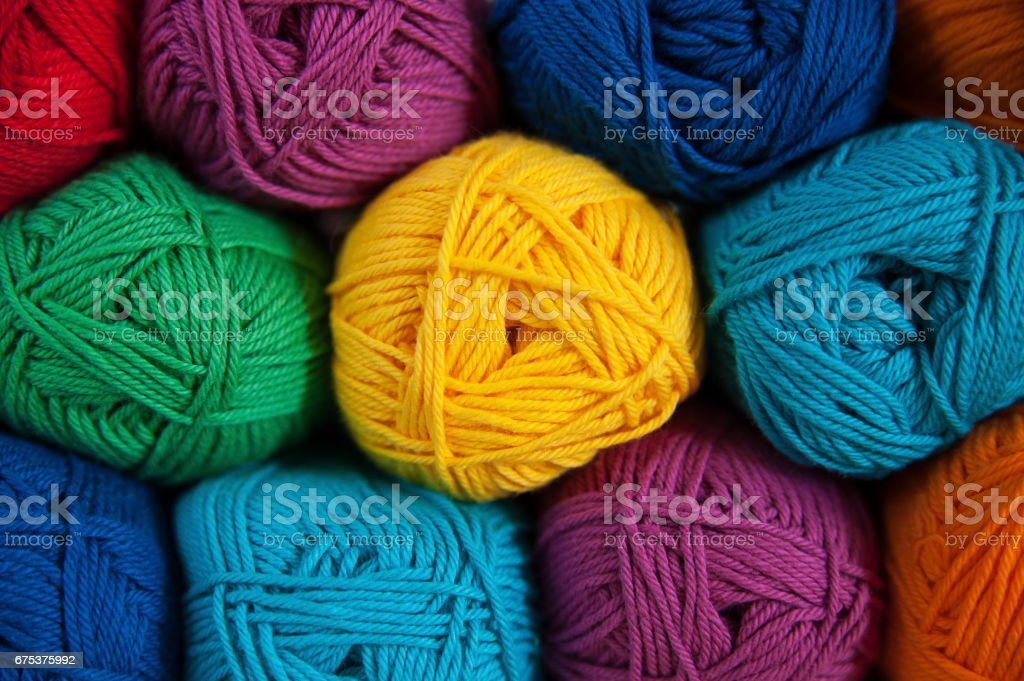 Symmetrically positioned rainbow colored cotton yarn background stock photo