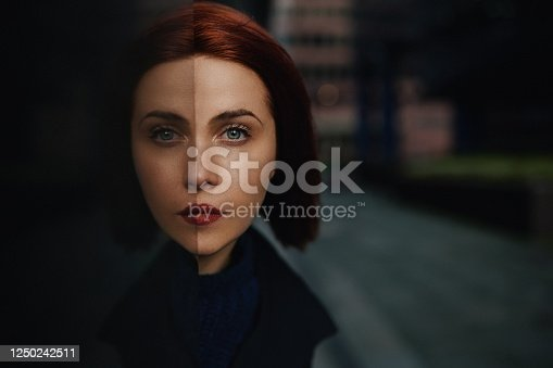 Redhead woman posing looking at the camera, reflection and symmetry concept