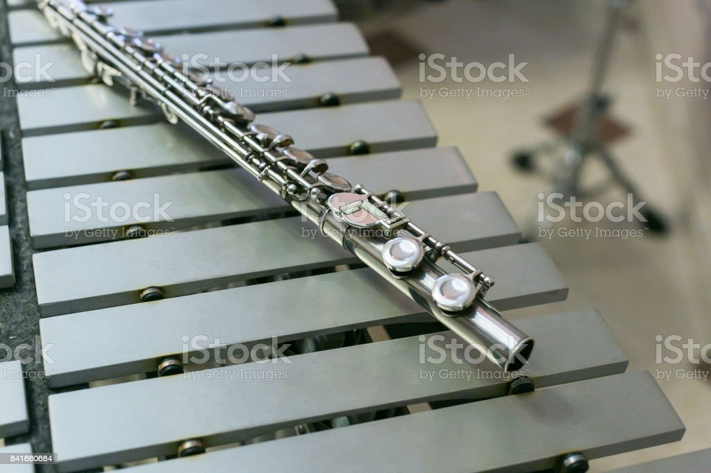 symphonic and brass band, percussion and wind instruments concept - beautiful closeup on shiny western concert flute lies on xylophone, education and orchestra concert, beige bars without mallets stock photo