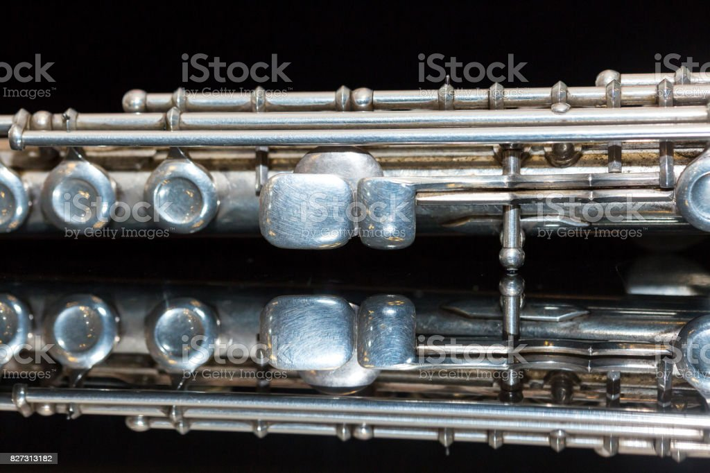 symphonic music concept - closeup on western concert flute lies on the pure black mirror surface, middle body section of instrument with majority of keys, marching, orchestra concerts, macro stock photo