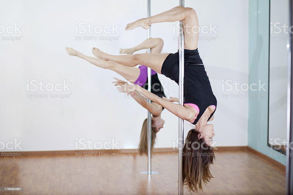 Synchronized pole dancers stock photo