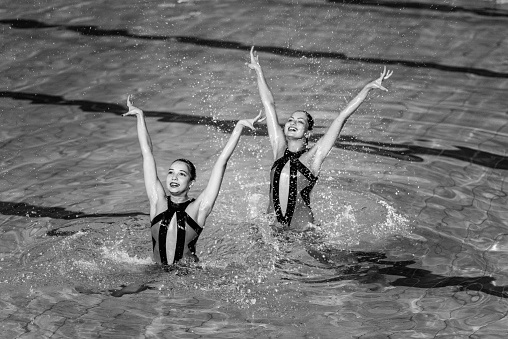 Synchronized swimming competition, duet performing. Black and white