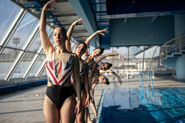 Synchronized swimming team on the side of the pool stock photo