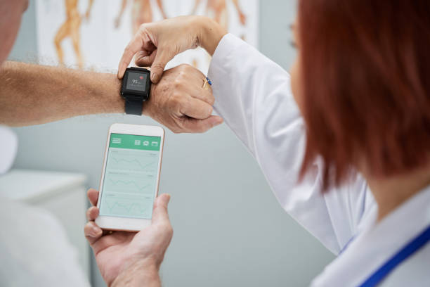 Synchronizing devices Doctor showing senior patient how to synchronize health app in smartphone and smartwatch medical equipment stock pictures, royalty-free photos & images