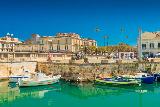 Syracuse, Italy: Cityscape of Syracuse and a small Island Ortygia, historical part of the city. Colorful boats lying on water near a stone pier stock photo
