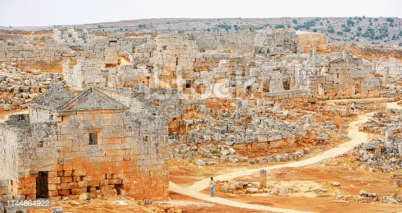 695022520 istock photo Syria before the war. Man crossing the Byzantine ruins of the Dead Cities, near Aleppo, in northern Syria. 1144864922