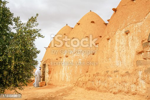 695022520 istock photo Syria before the war. Man entering a beehive house southwest of Aleppo in Syria. 1144649817