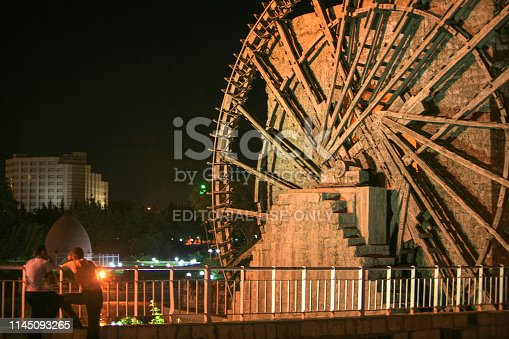 695022520 istock photo Syria before the war. People by the wooden giant water wheels of Hama by night. 1145093265