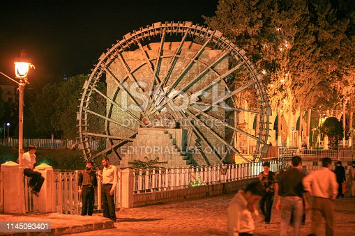 695022520 istock photo Syria before the war. People by the wooden giant water wheels of Hama by night. 1145093401