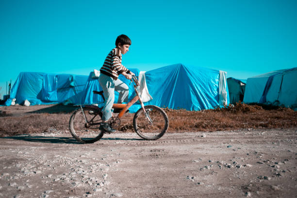 syrian little boy in refugee camp on a bike stock photo