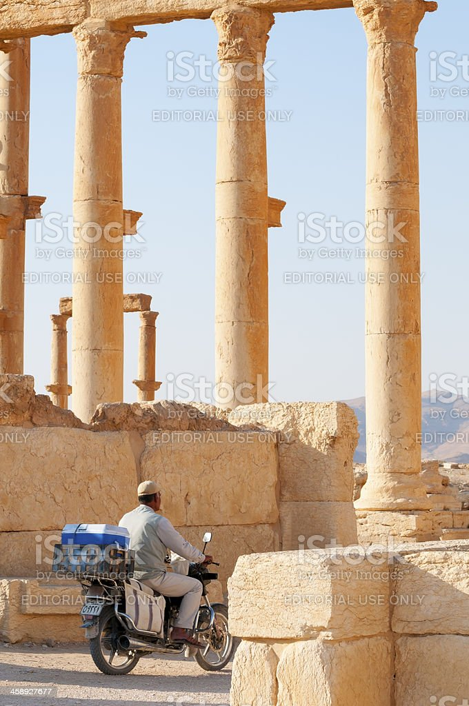 Riding a motorbike in Palmyra ruins of Syria royalty-free stock photo