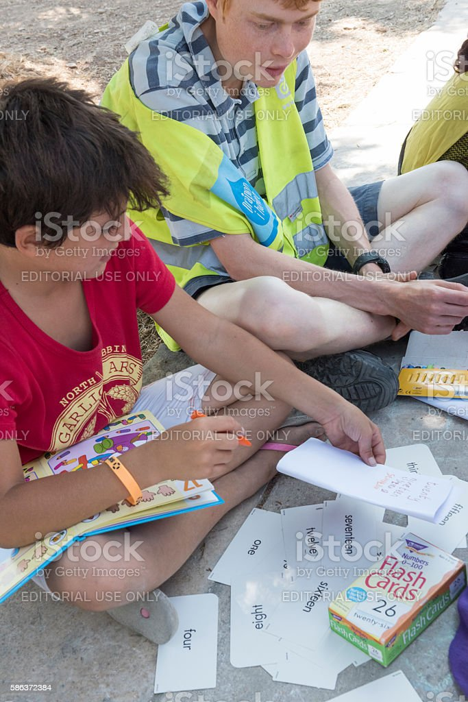 Syrian refugee boy learning to write in English stock photo